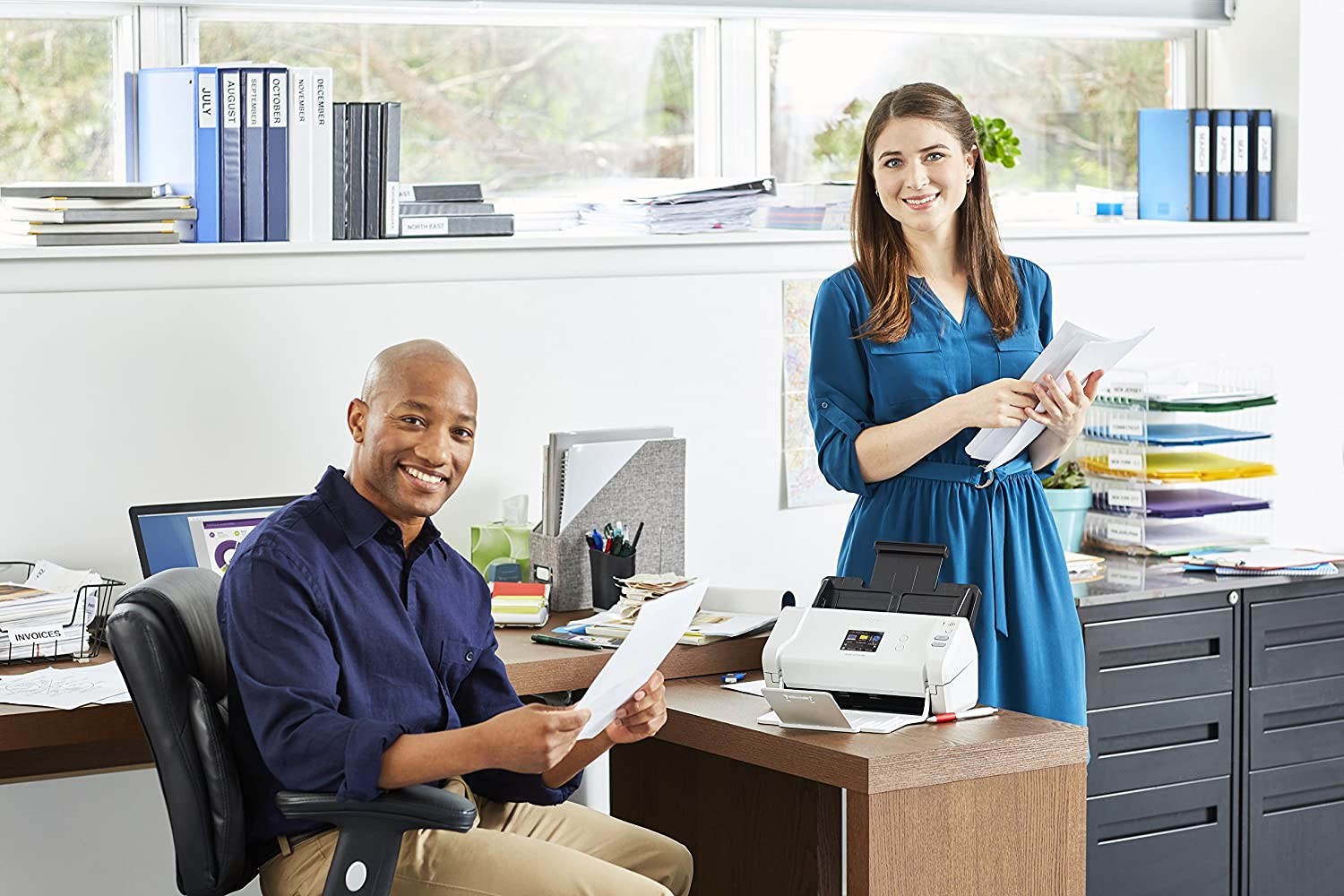 man sitting at a work desk and woman standing, both are smiling and holding sheets of paper