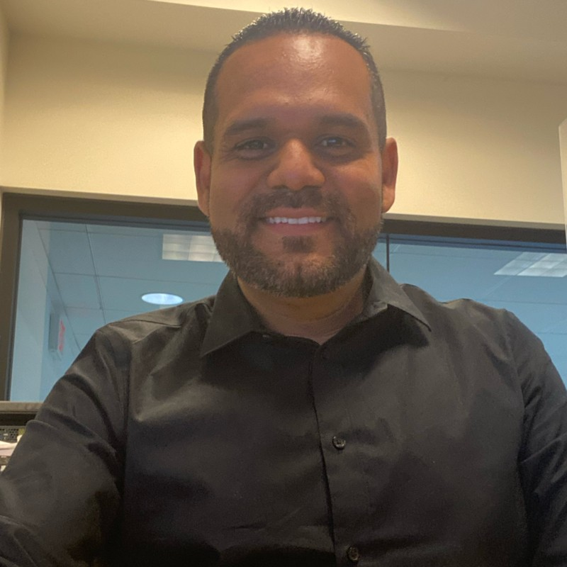 Nathan Banda wearing black button up shirt sitting in an office