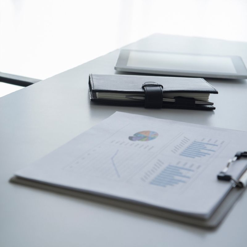 clipboard holding a pile of paper with a planner sitting next to it and an iPad farther behind that on a desk