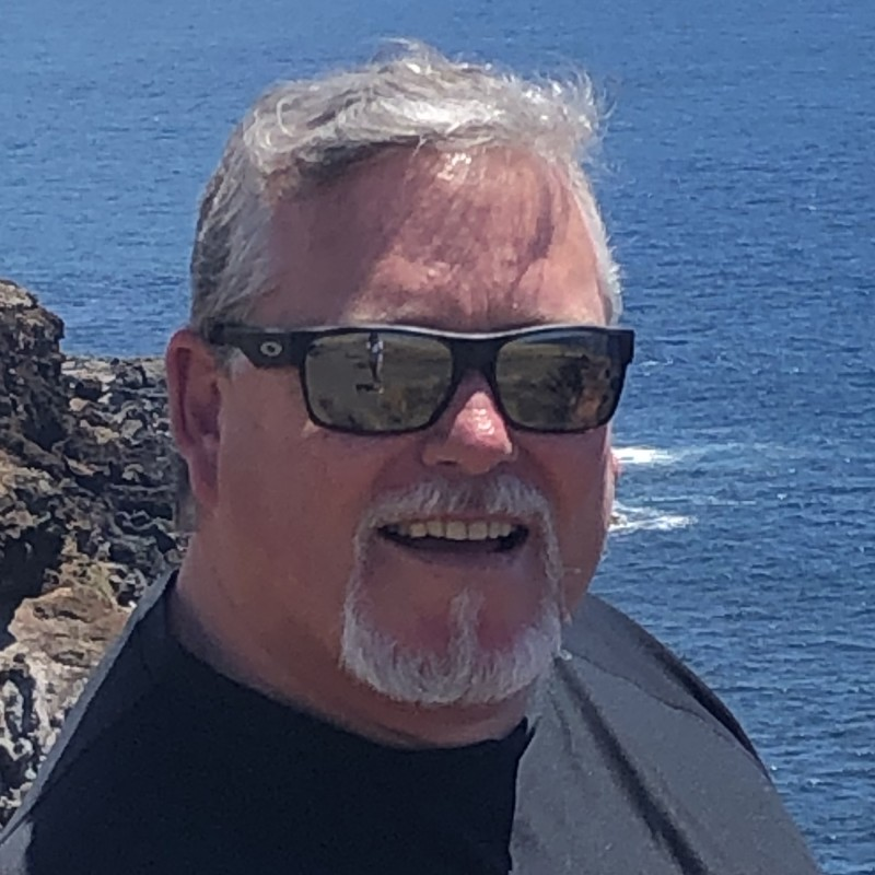 Thomas Kirk Vice President Fixed Operations wearing sunglasses with the ocean and rocky seaside in the background