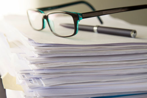 stack of paperwork with a pair of black glasses and pen sitting on top