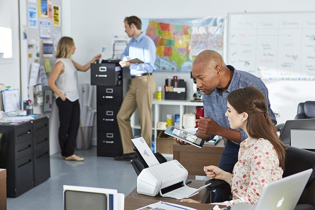 woman sitting at a desk with a man standing next to her, both are looking at a scanner while another man and woman stand at a file cabinet talking in the background