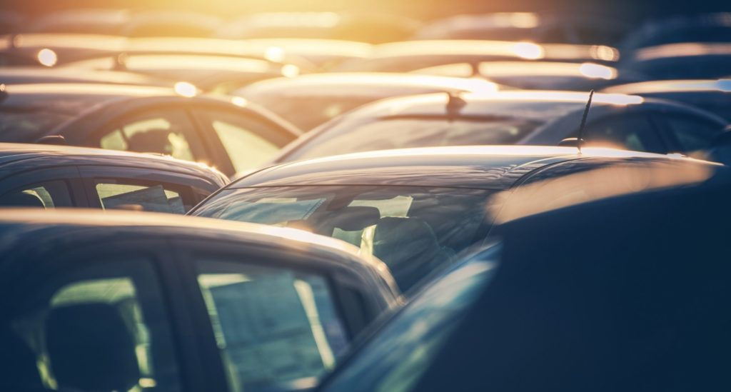 closeup of the top of cars sitting in a row and the sun setting in the back