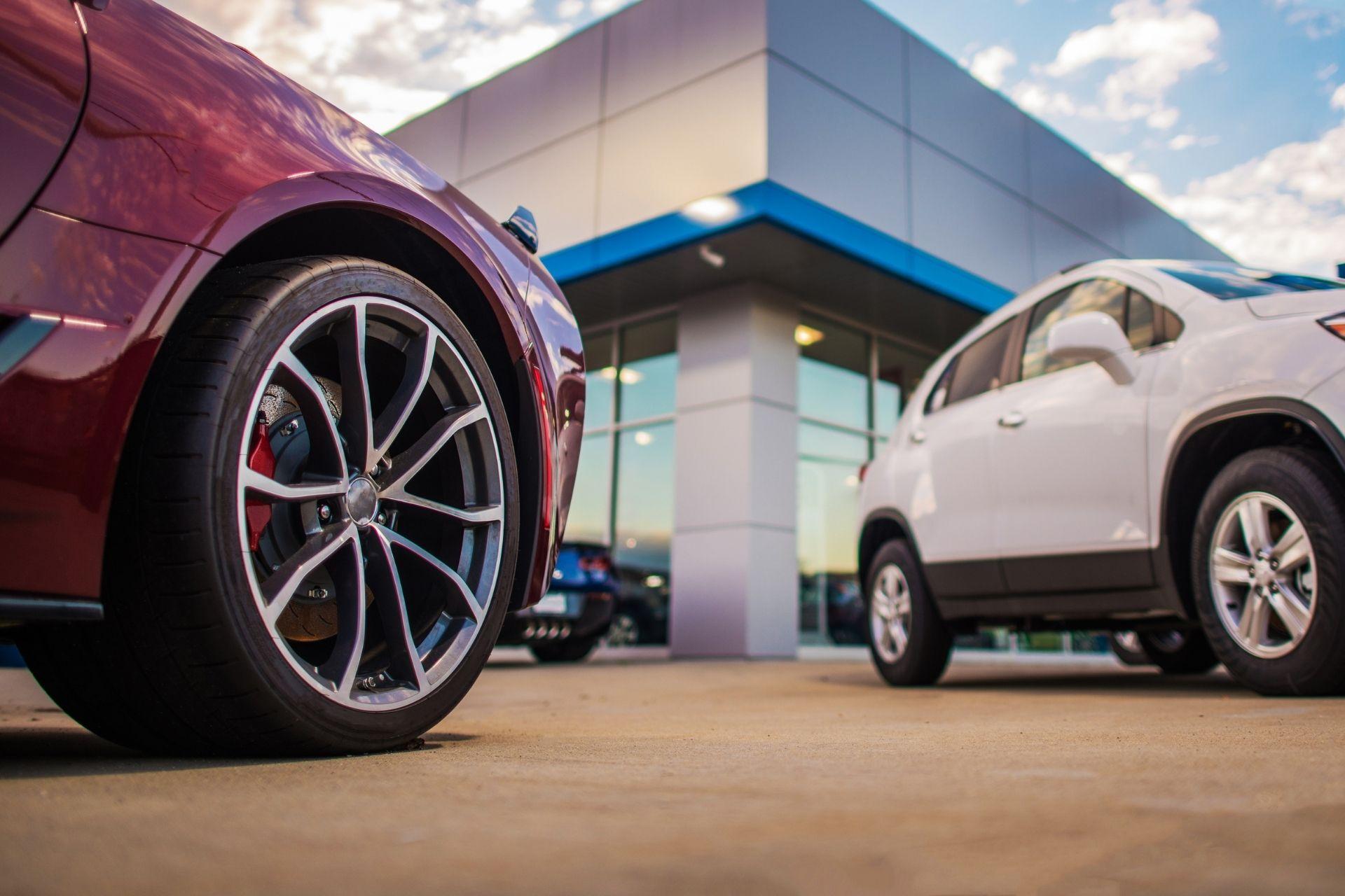closeup of two vehicles on a car dealership car lot