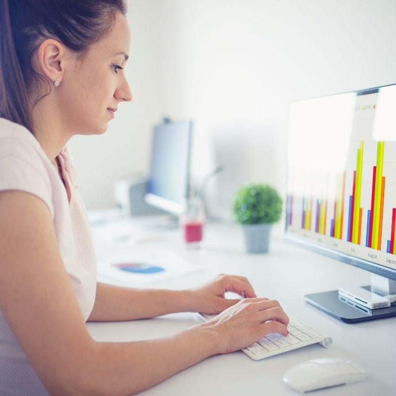 Woman working on an Apple desktop computer